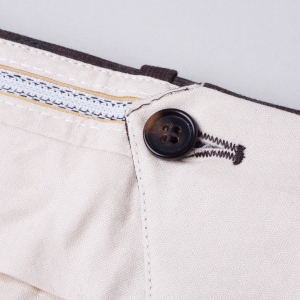 This button sits on the inside of the trouser lining, and keep the three points of contact for the two sides of the trousers in line for a consistent look.